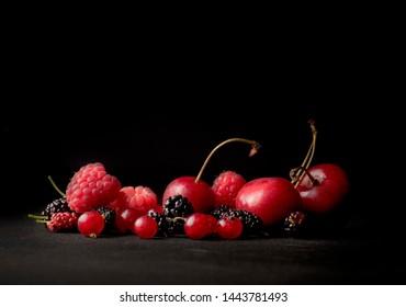 raspberries and mulberries, cherries and berries on a dark background, copy space