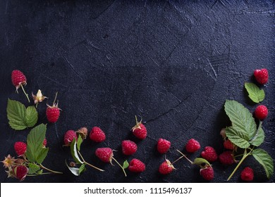 Raspberries on black background. Fresh ripe sweet berries. Selection of healthy food. Slate banner background. View from above, top studio shot, room for text