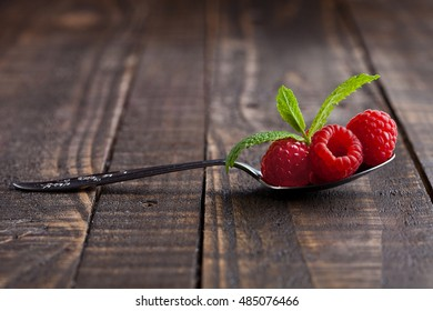 Raspberries on old spoon and mint on grunge wooden board. Natural healthy food. Still life photography