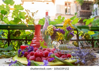 Raspberries on a table with flowers in cozy patio in Odessa