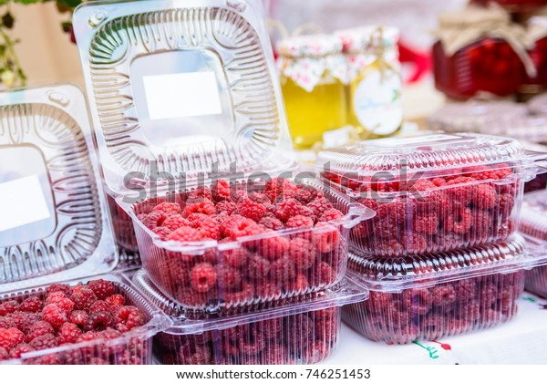 Raspberries in plastic box in supermarket