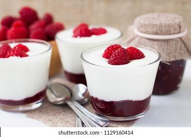 Raspberries and raspberry jam in fresh white yogurt. Detail view on three cups of refreshing snack