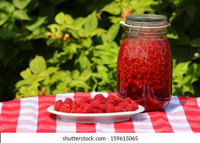 Raspberries and raspberry sirup in a glass jar on a red checkered tablecloth