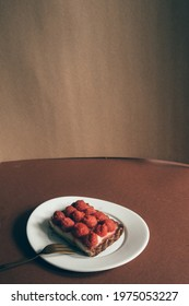 Raspberries rectangular shaped tart on a moody composition, with dark background,