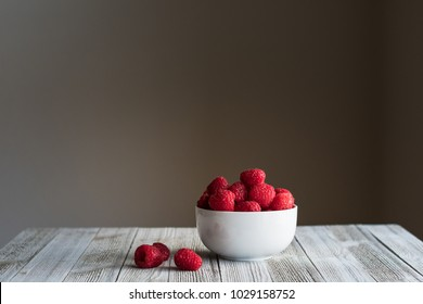 Raspberries in a small white bowl.