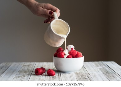 Raspberries in a small white bowl with cream being poured over them.