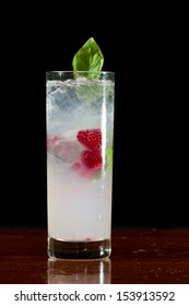 raspberry and basil cocktail served in a tall glass isolated on a black background