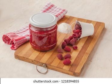 Raspberry berries and a jar of raspberry jam on a cutting board