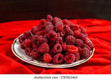 Raspberry berry lies on a plate on a red tablecloth