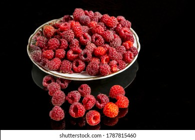 Raspberry berry on a white plate against a black background with reflection