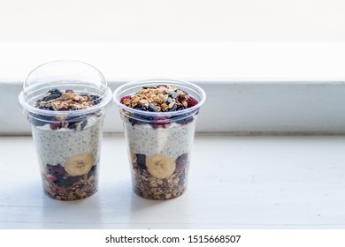 Raspberry and blackberry chia pudding served in plastic cups and ready to eat