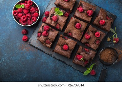 raspberry brownies  with fresh berries on blue background, top view