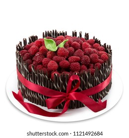 Raspberry cake with chocolate sticks and red ribbon on a white plate isolated on white background