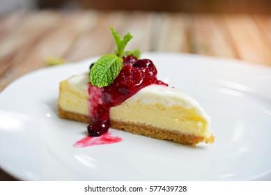Raspberry cheesecake with fresh cherry on white plate.