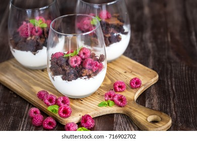 Raspberry and chocolate trifle desert on wooden background