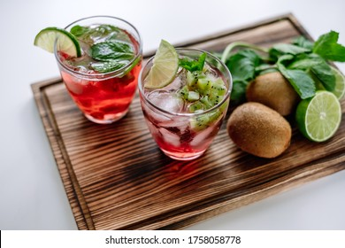 Raspberry cocktail, lemonade with lime, kiwi, mint and pieces of ice on a wooden board.