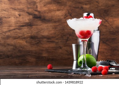 Raspberry daiquiri, alcoholic cocktail with white rum, lime juice, raspberries and crushed ice in tall glass, on wooden bar counter  with steel bar tools