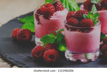 Raspberry granita with berries and mint in glass cups, selective focus and toned image