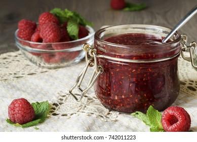 Raspberry jam in a glass jar with fresh raspberry berries