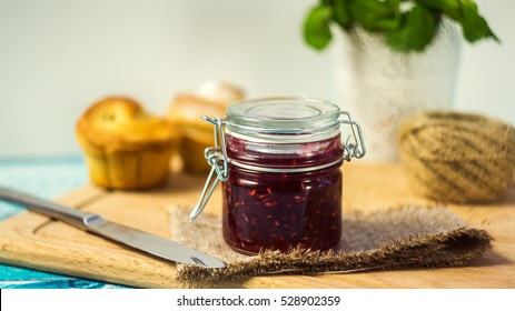 raspberry jam in a jar and muffins. selective focus