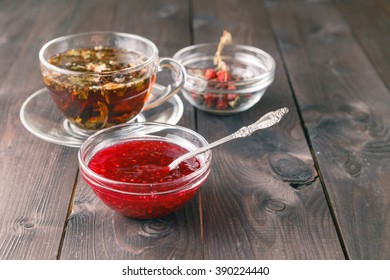 raspberry jam on table with cup of herbal tea