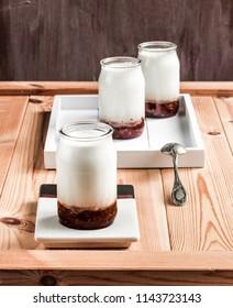 Raspberry jam yogurt on a wooden table board