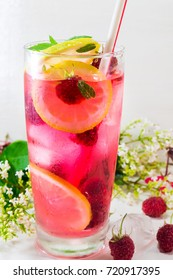 Raspberry juice with mint leafs and ice in a glass