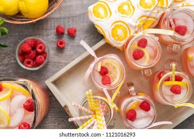 Raspberry lemonade garnished with fresh lemon and raspberries in drinking mason jars.