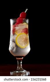 raspberry lemonade served in a stemmed glass on a dark bar