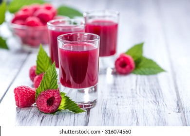 Raspberry Liqueur with some fresh fruits in a glass