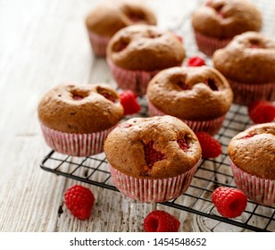 Raspberry muffins on a cooling tray on a wooden white table, close-up.  A delicious dessert or breakfast