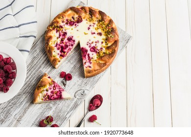 Raspberry pie with fresh raspberries on a wooden board on a light background. Horizontal orientation, top view with a copy space for the text. Holiday dessert.