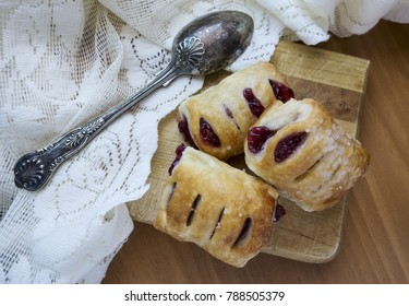 Raspberry puff pastries with sugar on top sitting n a wood board with antique spoon and lace.