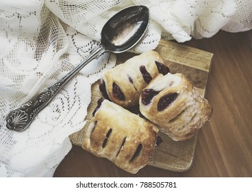 Raspberry puff pastries with sugar on top sitting on a wood board with antique spoon and lace.  Matte effect applied.