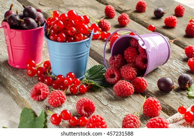 Raspberry, red currant and gooseberry in small buckets. Colorful small decorative buckets. The abundance of berries. Vitamins. Harvest. Background - old Board.