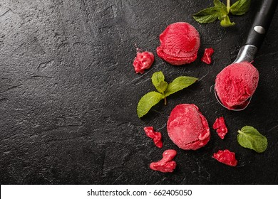 Raspberry red ice cream balls in ice cream spoon with mint over black background