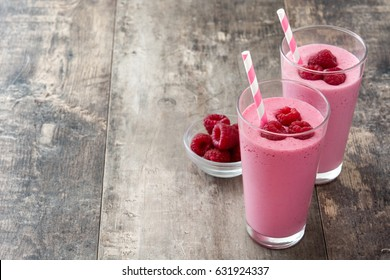 Raspberry smoothie in glass on wooden table