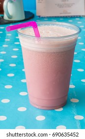 Raspberry Smoothie in a plastic cup with pink straw