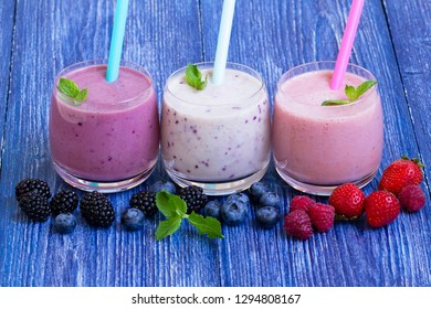 Raspberry, strawberry, blackberries, blueberry smoothie on blue wooden background. milkshake with fresh berries. healthy Breakfast. fruit smoothie with ingredients. well being and weight loos concept