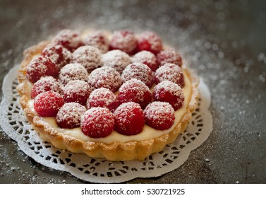 Raspberry tart on white doily on vintage looking surface, close up, isolated, selective focus