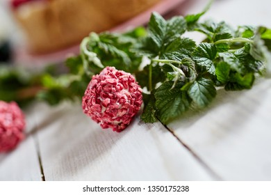 Raspberry truffle with raspberry branch on a wooden table