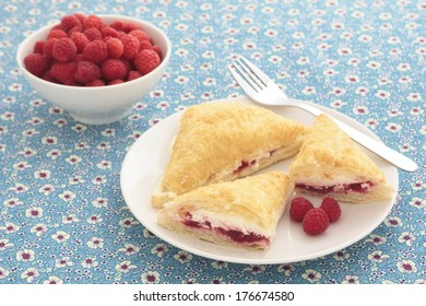 Raspberry turnovers on a plate, with a bowl of fresh raspberries in the background