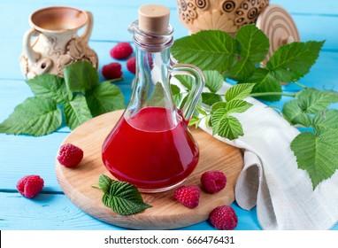 Raspberry vinegar on a wooden background