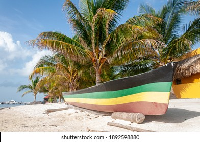 Rasta colors painted on a canoe that is sitting on a beach in Caye Caulker, Belize, Central America.