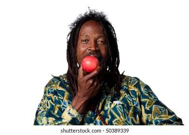 Rasta man eating an organic apple, studio shot
