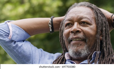 Rastafarian man relaxing with his head on his hands as he listens in a conversation