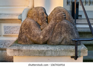 Rastede, Germany - April 09, 2019: stone skulptures of kissing lovers at the entrance of the historic palace (Palais) in evening sunlight
