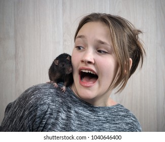 Rat on a girl's shoulder. Emotional portrait-fear, scream, vivid emotions from acquaintance with rodent