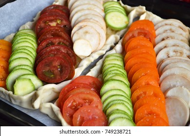 Ratatouille. Preparing vegetable tart with tomato, zucchini and eggplants. Pie with linearly laid vegetables. Cooking background.
