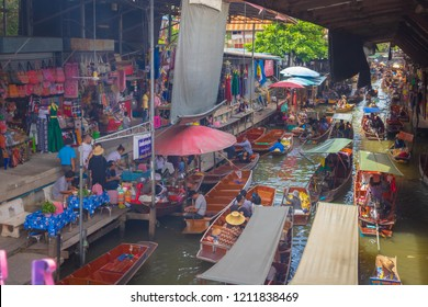Ratchaburi, Thailand - August 14th, 2017. Aerial view of Damnoen Saduak floating market filled with traditional boat in the river and crowd of tourists.